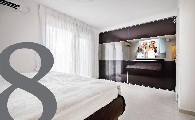 ארון הזזה זכוכית עם טלוויזיה מובנית במרכזו של חדר שינה לבן