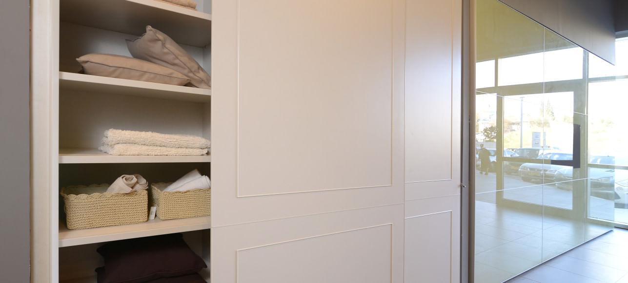 ארוך פרובנס רחב, דלת ההזזה פתוח וחושפת את תוכן הארון שמסודר על מדפיו הפנימיים